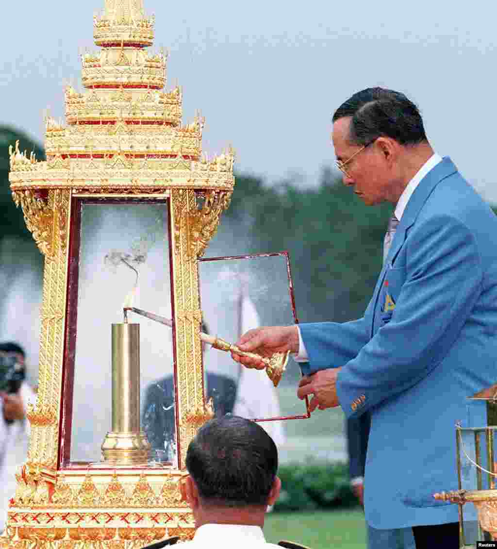 King Bhumibol lights the flame for the 13th Asian Games, Dec. 3, 1998, during a ceremony at Chitrlada Palace, the King's residence, during a ceremony three days prior to the start of the games.