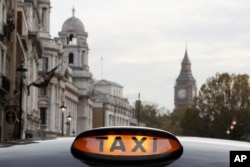 A taxi sign is lit up on a vehicle in London, Nov. 8, 2016.