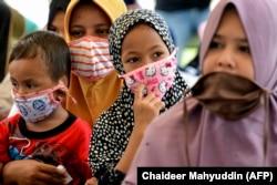 انڈونیشیا کے قصبے بلانگ بنڈانگ میں ماسک پہنے ہوئے بچے اور خواتین ضرورت مندوں میں خوراک تقسیم کر رہی ہیں۔ 20 جون 2020