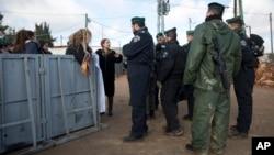 Warga di permukiman Amona di Tepi Barat tengah memberikan keterangan kepada polisi Israel, 1 Februari 2017. Militer telah memerintahkan warga untuk mengosongkan kawasan permukiman ini dalam waktu 48 jam. (AP Photo/Oded Balilty)