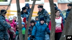 La policía evacúa a estudiantes en una escuela de Moscú.