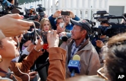 Carlos Catarldo Gomez, of Honduras, right, is surrounded by reporters after leaving the United States, the first person returned to Mexico to wait for his asylum hearing date, in Tijuana, Mexico, Jan. 29, 2019. The Trump administration has launched an effort to make asylum seekers wait in Mexico while their cases wind through U.S. immigration courts.