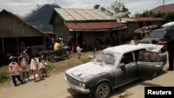 Warga desa berdiri di dekat mobil yang diselimuti debu, menunggu untuk dievakuasi, sementara gunung Sinabung di Karo, Sumatera Utara terus mengeluarkan debu dan lava panas(15/9).
