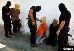 Các phần tử chủ chiến Hamas chuẩn bị hành hình những người Palestine bị cáo buộc hợp tác với Israel
