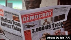 In this file photo, a man reads a news paper with headlines comment on American President Barrack Obama announcement on sending troops to fight the Ebola virus in Monrovia, Liberia, Wednesday, Sept. 17, 2014. (AP Photo/Abbas Dulleh)