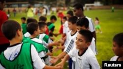 Anak-anak Israel dan Palestina saling bersalaman sebelum pembukaan program pelatihan sepakbola kedua negara yang diluncurkan oleh Peres Center for Peace, di Kibbutz Dorot, di luar Jalur Gaza, 2014. (Reuters/Amir Cohen)