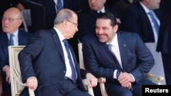 Saad al-Hariri talks with Lebanese President Michel Aoun while attending a military parade to celebrate the 74th anniversary of Lebanon's independence in downtown Beirut, Lebanon, Nov. 22, 2017.
