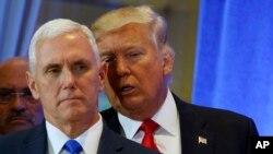 Tổng thống tân cử Donald Trump trao đổi với Phó Tổng thống tân cử Mike Pence trong một cuộc họp báo tại Tháp Trump.