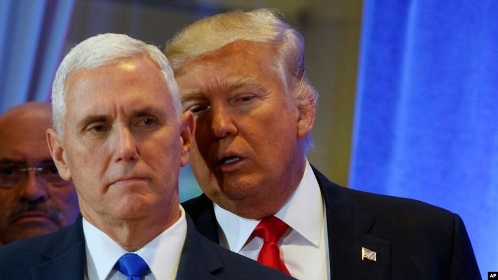 Le président élu des Etats-Unis Donald Trump, arrière-plan, soufle quelques choses à l'orielle de son vice-président Mike Pence lors d'une conference de presse à la tour Trump, à New York, 11 janvier 2017.