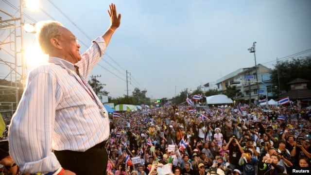 Protest leader Suthep Thaugsuban greets a crowd of anti-government protesters before making an address outside Government House in Bangkok, Dec. 9, 2013.