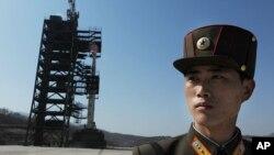 ေျမာက္ကိုးရီးယား အေစာင့္ စစ္သား တစ္ဦး အား တုန္ခ်မ္းရီး (Tongchang-ri) အာကာသ စခန္းရွိ အြန္ဟာ-သံုး (Unha-3 Rocket) ဒံုးပ်ံ အနီး ေတြ႔ရစဥ္