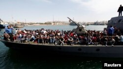 Des migrants clandestins, secourus par la garde-côte libyenne, transportés à bord d'un bateau au port de Tripoli, Libye, 10 mai 2017.