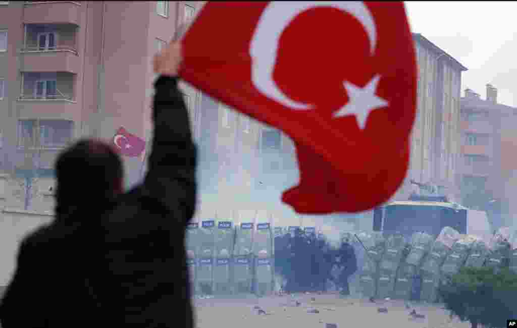 A man, holding a national flag with a poster of Turkey's founder Kemal Ataturk, watches as thousands of Turks clash with security as they try to break through barricades mounted around the prison and courthouse complex in Silivri, in the outskirts of Istanbul.