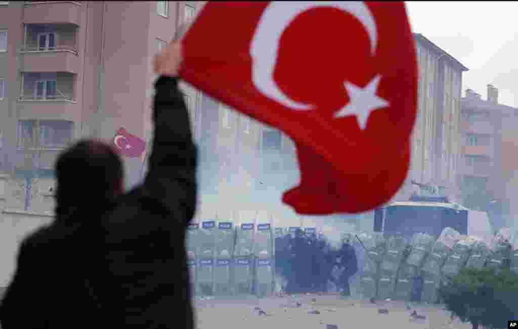 Một người trương lá cờ Thổ Nhĩ Kỳ giữa lúc hàng ngàn người biểu tình đụng độ với nhân viên an ninh khi định vượt qua rào cản được dựng lên chung quanh khu nhà tù và tòa án tại Silivri, thuộc vùng ngoại ô Istanbul.