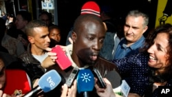 FILE - A Senegalese man named Ngame, who told reporters in Roqeutas de Mar, Spain, that he was rescued by Spain's coast guard, was one of 35 African migrants among the lottery's top prize winners; he won $438,000, Dec. 22, 2015.
