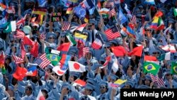 Graduating students from the School of International and Public Affairs at Columbia University wave flags during a graduation ceremony in New York, Wednesday, May 17, 2017.