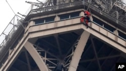 A rescue worker, top in red, hangs from the Eiffel Tower while a climber is seen below him between two iron columns Monday, May 20, 2019 in Paris.