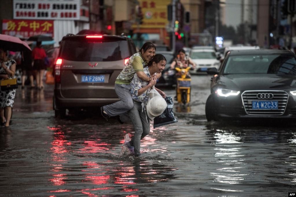 中国沈阳,暴雨过后,一位女子背着上了年纪的妇女趟水过街(2017年7月14日)