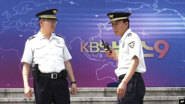 South Korean police officers stand guard in front of the Korea Broadcasting System (KBS) building in Seoul, South Korea, June 4, 2012.