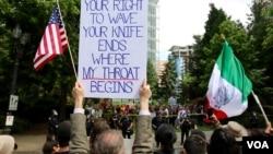 Sebuah kelompok pro imigran melakukan aksi unjuk rasa tandingan di depan unjuk rasa kelompok anti imigran di Portland, Oregon. (R. Taylor/VOA)