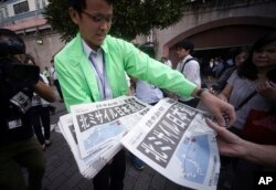A man distributes an extra edition of a newspaper reporting about North Korea's missile launch, at Shimbashi Station in Tokyo, Sept. 15, 2017.