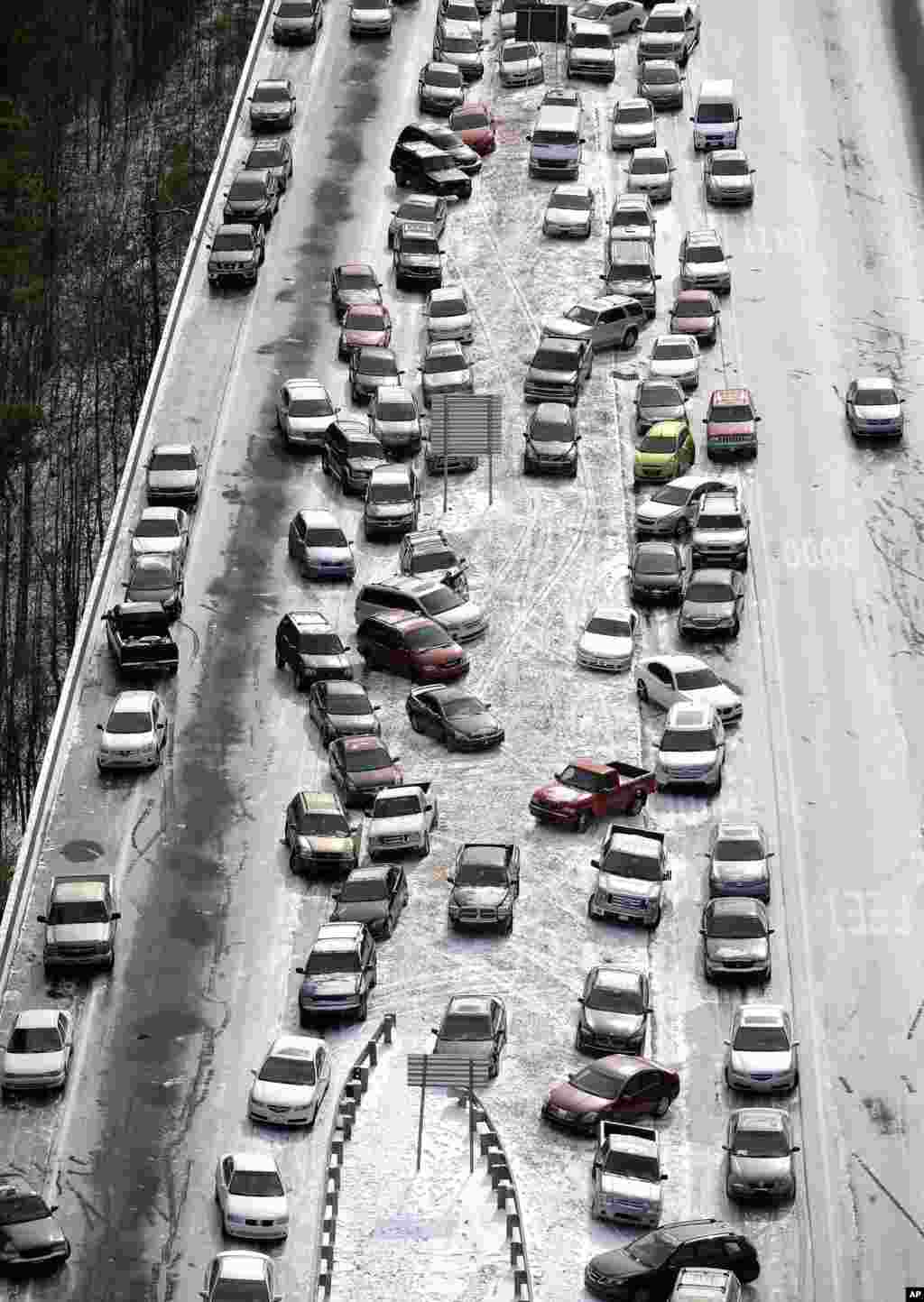 Abandoned cars on I-75 headed northbound near the Chattahoochee River overpass are piled up in the median of the ice-covered interstate after a winter snow storm in Atlanta, Georgia, USA. Georgia Gov. Nathan Deal said that the National Guard was sending military Humvees onto Atlanta's snarled freeway system in an attempt to move stranded school buses and get food and water to people.