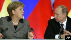 Russian President Vladimir Putin, right, and German Chancellor Angela Merkel speaks to each other after a signing ceremony during a Russian-German business forum in the Grand Kremlin Palace in Moscow, Friday, Nov. 16, 2012.