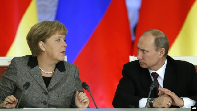 Russian President Vladimir Putin, right, and German Chancellor Angela Merkel speak to each other after a signing ceremony during a Russian-German business forum in the Grand Kremlin Palace in Moscow, Friday, Nov. 16, 2012.