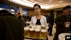 FILE - A North Korean waitress prepares to serve beer at the Mansugyo Soft Drink restaurant in Pyongyang.