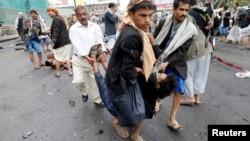 Pemberontak Syiah Houthi membawa korban yang terluka akibat serangan bom bunch diri di Sanaa (9/10).