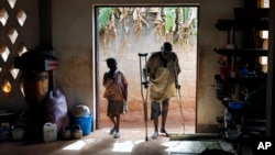 FILE - An elderly Muslim refugee uses crutches to walk next to a youth inside a Catholic church in Carnot, Central African Republic, April 2014.