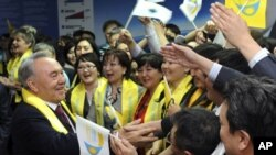 """Kazakh President Nursultan Nazarbayev (L) greets supporters during the """"Forward, together with the leader"""" forum in Astana, April 4, 2011"""
