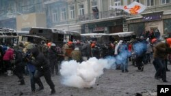 Protesters run away from a stun grenade as they clash with police in central Kyiv, Jan. 22, 2014.
