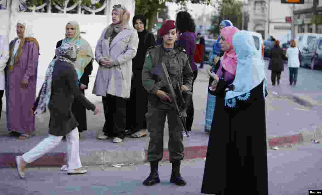 People stand in line at a polling station as they wait to cast their votes, in Tunisia, Oct. 26, 2014.