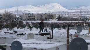 A Syrian girl stands on top of her tent to remove the snow from it at a refugee camp in Zahleh, Bekaa Valley, east Lebanon, Jan. 8, 2015.