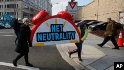 """Protesters carry the top of an alarm clock display that reads """"Net Neutrality"""" after a protest at the Federal Communications Commission in Washington, Dec. 14, 2017. (AP Photo/Carolyn Kaster)"""