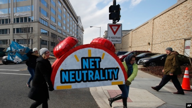 """Protesters carry the top of an alarm clock display that reads """"Net Neutrality"""" after a protest at the Federal Communications Commission in Washington, Dec. 14"""
