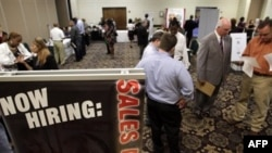 In this July 13, 2011 photo, National Tire & Battery area director Don Hudome, right, meets with an attendee at a National Career Fairs Job Fair, in Dallas. More people applied for unemployment benefits last week, evidence that layoffs are rising and the