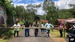 In this April 24, 2020, photo, provided by the Indigenous People Alliance of the Archipelago, indigenous peoples from the Buntao' community in Indonesia's North Toraja regency in South Sulawesi Province use a wooden barrier to block off their village. (AMAN via AP)