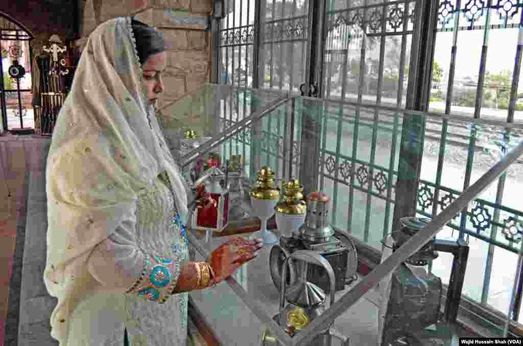 ایک خاتون عجائب گھر کے شوکیس میں رکھی ہوئی چیزوں کو دیکھ رہی ہے۔
