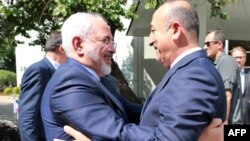Turkish Foreign Minister Mevlut Cavusoglu, right, welcomes Iranian counterpart Mohammad Javad Zarif at the foreign ministry in Ankara, Aug. 12, 2016.
