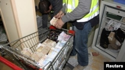 "A policeman puts money bills into a trolley at Fuenlabrada outside Madrid, October 16, 2012, during an ""Operation Emperor"", which dismantled a gang integrated by Chinese nationals and allegedly laundered an estimated 160 million euros a year, Spanish police said."
