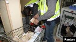 一名西班牙警察在这次搜查行动中把搜获钱币放进推车