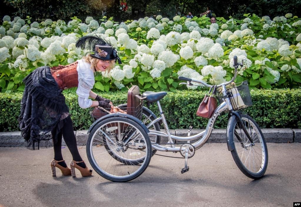 """在莫斯科的索科尔尼基公园,第五届""""女士骑自行车节""""活动的参与者从三轮车后篮中拿东西。该节日的目的是展示城市时尚女性和复古风格的自行车 (2017年8月6日)"""
