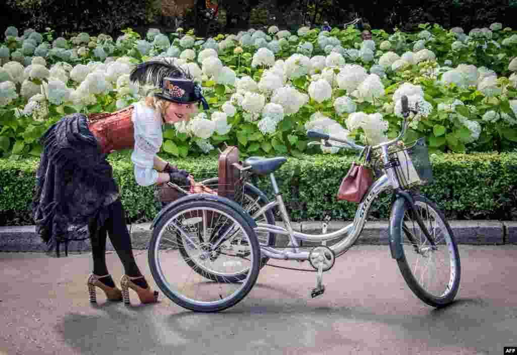អ្នកចូលរួមនៅក្នុងពិធីបុណ្យ Lady on Bicycle ប្រចាំឆ្នាំលើកទី៥បើកកាតាបរបស់នាងនៅក្នុងខាងក្រោយកង់នៅក្នុងឧទ្យាន Sokolniki ក្រុងមូស្គូ ប្រទេសរុស្ស៊ី។