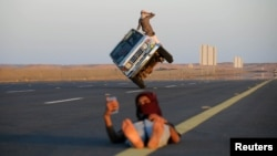 """Saudi men perform a stunt known as """"sidewall skiing"""" (driving on two wheels) as a youth takes a selfie in Tabuk, Saudi Arabia March 11, 2018."""