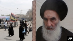 FILE - Shii'te pilgrims make their way to the shrine of Imam Moussa al-Kadhim as passing by a poster of Shi'ite spiritual leader Grand Ayatollah Ali al-Sistani, right, in Baghdad, Iraq.
