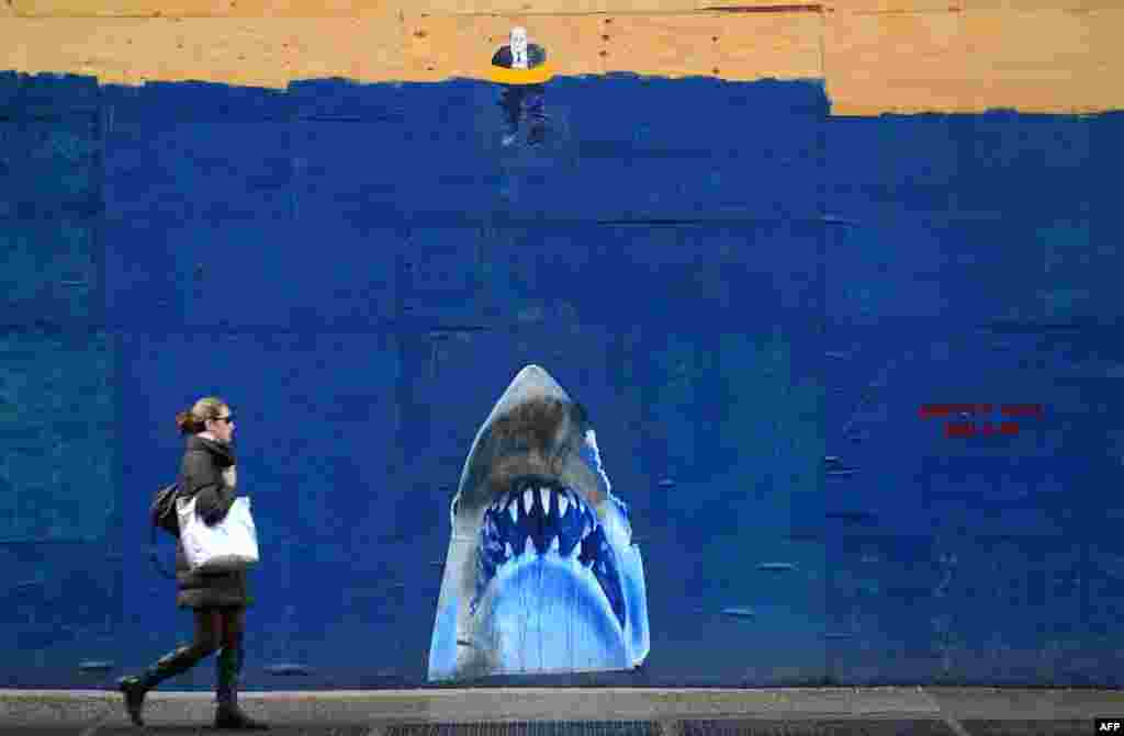 A woman walks past a street mural in New York.