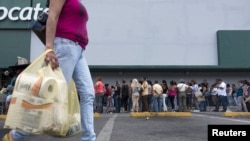 FILE - A woman carries bags with toilet paper rolls as people line up to buy staple items at a Makro supermarket in Caracas Aug. 4, 2015.