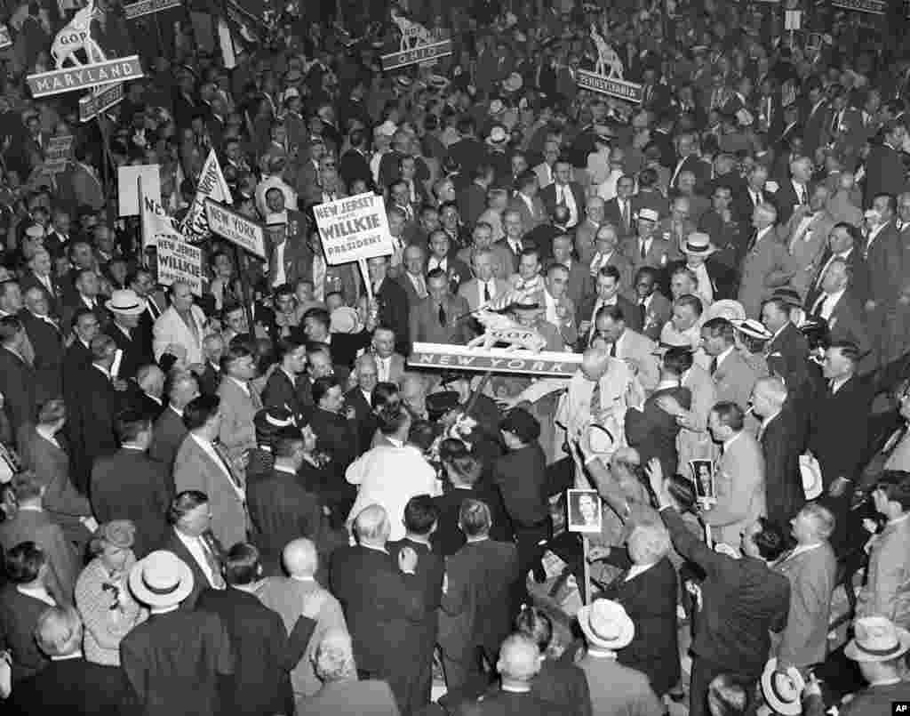 FILE - Thomas Dewey and Wendell Willkie supporters in the New York delegation attempt to seize the New York State banner at the Republican National Convention in Philadelphia, June 26, 1940. The scene followed the nomination of Willkie for the presidency.